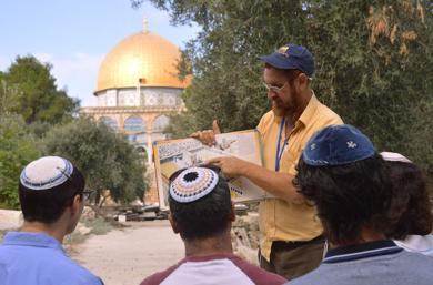 <p>Yehuda Glick, a Temple Mount activist prior to becoming a Knesset member, showing religious Jews a diagram of the Jewish temple that stood where the Dome of the Rock now stands in Jerusalem, Sept. 17, 2013. (Christa Case Bryant/The Christian Science Monitor/Getty Images)</p>