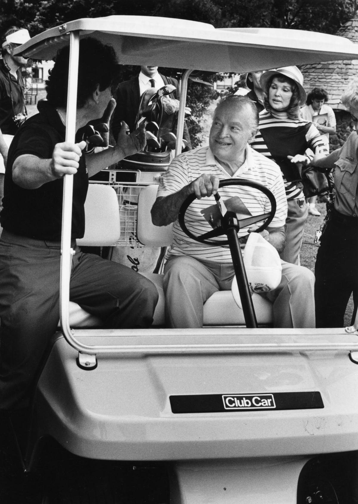 Bob Hope sits behind the wheel of a golf cart as Don Angell, president ...