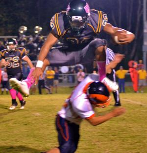 <p>ANDREW BYNUM hurdles over Starmount's Nazy Serrano in Wilkes Central's win on Friday night. Despite being flagged on the play, Bynum rushed for a game-high 173 yards and two touchdowns.</p>