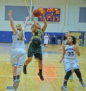 <p>KAMRE GIBBS flies through the air against Smoky Mountain's Reanna Lehmann (32) and Aaliyah McCollum during Wilkes Central's 56-52 win in the third round of the 2-A state playoffs. Gibbs, who led Central with 15 points, went 8-of-8 from the free-throw line.</p>