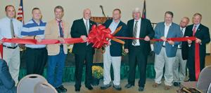 <p>GATHERED FOR A RIBBON CUTTING for the dedication of the new Wilkes County Agriculture Center in Wilkesboro are, left to right, Wilkes Cooperative Extension Agent John Cothren; Wilkes County Commissioners David Gambill, Gary Blevins, Eddie Settle (chairman) and Keith Elmore; N.C. Agriculture Commissioner Steve Troxler; County Commissioner Greg Minton; Wilkes Cooperative Extension Director Bill Hanlin and Dale Folwell, N.C. assistant secretary of employment security.</p>