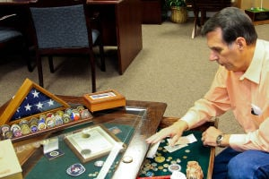 Coins (1): North Side Baptist Church Pastor Olton Phillips examines his personal coin collection in his office at the church Friday, Dec. 20, 2013. - Jodi Perry