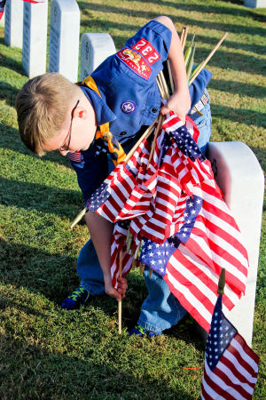 Veterans Day - Scouts: Nathan Peterson, 7, of Boy Scout Troop 232 places a flag next to a headstone at the Central Texas Veterans Cemetery on Monday, Nov. 11, 2013, in honor of Veterans Day. - Jodi Perry | Herald