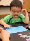 Joel Jung, 4, listens during a bingo game Aug. 21 at the library. Participants had a chance to win school supplies.