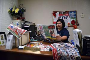 <p>Roxanne Flores, youth programs specialist for Killeen, looks over ads for Black Friday sales Wednesday.</p>
