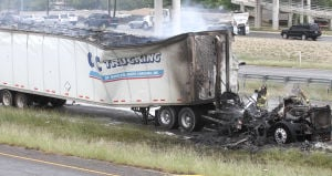 Truck Fire: Firefighters hose down at 18-wheeler after it caught fire Monday afternoon on eastbound U.S. Highway 190 near Fort Hood Street in Killeen. - Photo by Herald/MARIANNE LIJEWSKI