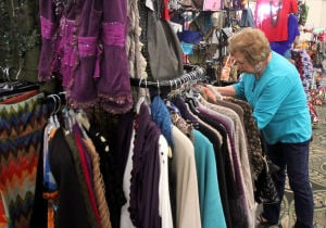 Fort Hood Officers' Spouses Club Holiday Bazaar: Carolina Chapa looks over a selection of clothing while shopping at the Fort Hood Officers' Spouses Club holiday bazaar Sunday, Nov. 17, 2013, at the Killeen Civic and Conference Center. - Photo by Herald/CATRINA RAWSON