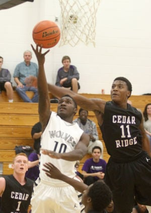 Boys Basketball: Shoemaker V. Cedar Ridge: Shoemaker's Qwoy Blunt attempts a basket against Cedar Ridge's De'andre Davis Monday night at Shoemaker. - Herald/MARIANNE GISH