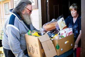My Brother's House Food Pantry: Volunteer Ilse Waggoner, right, helps Kempner resident Clyde Henry transport his box of food from My Brother's House food pantry Tuesday, Nov. 19, 2013. - Jodi Perry | Herald