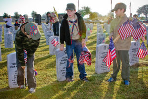 Veterans Day - Scouts: Boy Scouts Evan Jefferson, 9, Jaden Minton, 10, and Aiden Jefferson, 10, from Troop 255 place flags on graves at the Central Texas Veterans Cemetery on Monday, Nov. 11, 2013, in honor of Veterans Day. - Jodi Perry | Herald
