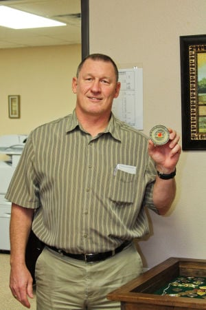 Coins (4): On Dec. 20, North Side Baptist Church Director of Children's Programs, Dale Cowan, shows one of the many coins that has been collected as part of the Master Club Program. - Photo by Jodi Perry