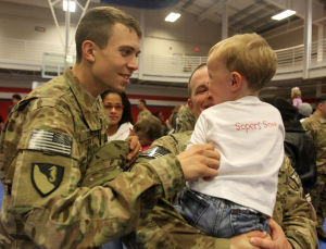 937th Route Clearance Company Homecoming: Spc. Landon Soper, 937th Route Clearance Company, 8th Engineer Battalion, 36th Engineer Brigade, holds his son, Gauge, 2, as his friend and fellow soldier Spc. Stephen Thompson talks with him at a homecoming ceremony Monday, Nov. 4, 2013, at the West Fort Hood Physical Fitness Center. - Herald/CATRINA RAWSON