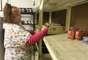 Harker Heights Food Pantry: Linda Dawson, director of the Harker Heights Food Pantry, places newly donated items on the bare shelves Tuesday, Nov. 12, 2013, at the First Baptist Church in Harker Heights. - Herald/CATRINA RAWSON