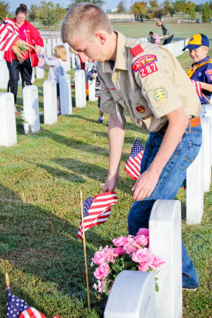 United Way - Boy Scouts: Boy Scout Samuel Miller, 17, places flags on graves at the Central Texas State Veterans Cemetery on Monday, Nov. 11, 2013, in honor of Veterans Day. - Jodi Perry | Herald
