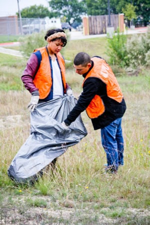 3rd CR: Pvt. Faye Tuufuli and Pfc. Michael West, with the 3rd Cavalry Regiment, pick up trash along Clore Road in Harker Heights during a  Make A Difference Day project Saturday morning. - Photo by Jodi Perry