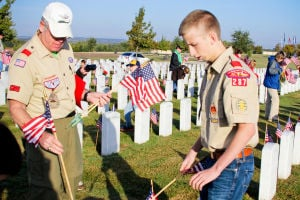 Veterans Day - Scouts: Boy Scout Troop 287 leader, Dennis Duffey, assists Boy Scout Samuel Miller, 17, as he places flags on graves at the Central Texas Veterans Cemetery on Monday, Nov. 11, 2013, in honor of Veterans Day. - Jodi Perry | Herald