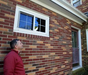 RIDDING HOME OF NUISANCE ANIMALES: Animal removal expert Brian Briggs inspects a home in Akron, Ohio, that shows damage from squirrels. Briggs' company, Frontline Animal Removal, rids home of nuisance animals. - ED SUBA JR. | Akron Beacon Journal