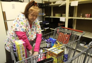 Harker Heights Food Pantry: Linda Dawson, director of the Harker Heights Food Pantry, places newly donated items on the bare shelves Tuesday, Nov. 12, 2013, at the First Baptist Church in Harker Heights. - Photo by Herald/CATRINA RAWSON