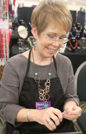 Fort Hood Officers' Spouses Club Holiday Bazaar: Dale Koebnick, owner of the Bead Bistro, works on a ring while selling her merchandise at the Fort Hood Officers' Spouses Club holiday bazaar Sunday, Nov. 17, 2013, at the Killeen Civic and Conference Center. - Herald/CATRINA RAWSON