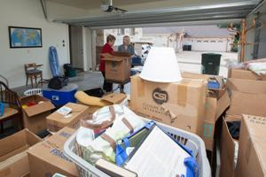 <p>Homeowner Martha Tyroc and Professional Organizer Lauren Weldon search through a box of some memorabilia in Mrs. Tyroc's Garage Monday morning during an organizing session. Mrs. Tyroc has hired Lauren Weldon Organized Interiors to help assist her in clearing and organizing some of the unnecessary items in her home.</p>