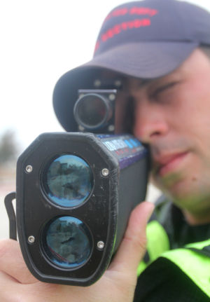 Killeen Police Officer Traffic Control: Killeen police officer Garlen Henning holds a laser radar gun to catch speeding drivers while working his shift Friday in Killeen. The city has more than doubled the number of tickets written this year compared to 2012, with extra patrol hours spent on traffic enforcement funded by a state grant. - Herald/CATRINA RAWSON