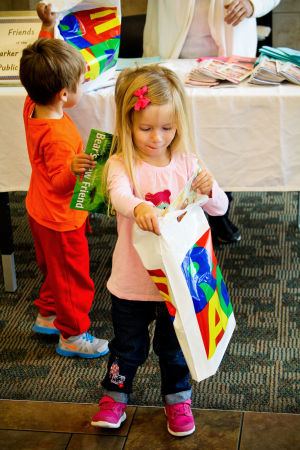 Early Literacy Fair: Three year old Alessandra Macy checks out the goodie bag that she received at the Early Literacy Fair held at the Stewart C. Meyer Library on November 20th. - Jodi Perry | Herald