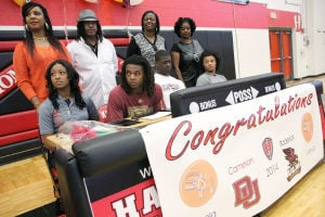 Heights Basketball Signings: Harker Heights' Angela Delaney, left, Cameron Delaney, middle left, Roderick Taylor, middle right, and Josh Delaney, right, listen to a coach before they sign letters of intent to play basketball at their respective colleges Wednesday afternoon at the high school. - Photo by Herald/MARIANNE GISH