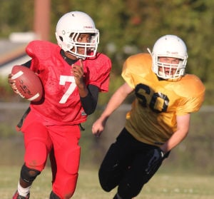 Future Stars Football: Manor's Jaden James runs with the ball as Smith's Kenneth Pearce chases him down during Tuesday's eighth-grade game at Manor. - Photo by Herald/CATRINA RAWSON