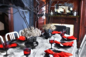 Homes-Designer-Halloween Parties: Bare branches, spray-painted black and secured in vases with gravel, floral foam and a layer of moss make a stunning and inexpensive Halloween centerpiece for parties. - Photo by Scripps Networks Interactive