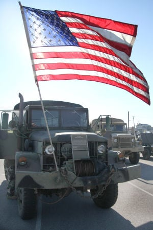 Mounted Warfare Historic Vehicle Rally: A M35A2 2½-ton truck holds an American flag during the Mounted Warfare Historic Vehicle Rally Friday morning on TJ Mills Boulevard. - Herald/MARIANNE LIJEWSKI