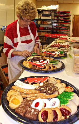 Heidi's German Bakery: Margit Spriggs finishes a custom Christmas platter with from-scratch, authentic German cookies, pastries and cakes at Heidi's German Bakery. - Photo by Steve Pettit | Herald
