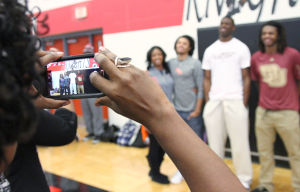 Heights Basketball Signings: A parent takes a picture of Harker Heights' Angela Delaney, left, Josh Delaney, middle left, Roderick Taylor, middle right, and Cameron Delaney, right, before they sign letters of intent to play basketball at their respective colleges Wednesday afternoon at the high school. - Photo by Herald/MARIANNE GISH