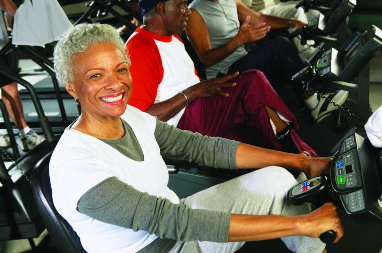 Senior woman using cycling machine in gym, smiling, portrait