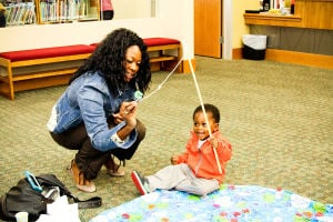 Early Literacy Fair: Monica Evans works on letter recognition with her son, Joshua (2), at a fishing station during the Early Literacy Fair held at the Stewart C. Meyer Library on Wednesday morning. - Jodi Perry | Herald