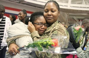 III Corps & 3CR Homecoming: Staff Sgt. Kizzie Brown, III Corps, hugs her daughter Kira Brown during the III Corps and 3rd Cavalry Regiment Homecoming Sunday night at West Fort Hood. - Photo by Herald/MARIANNE GISH
