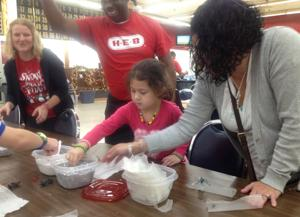 """<p>Fred Williams cheers on volunteer Courtney Aregood as she helps Kayla Steimle, 6, and her mother, Christina Steimle, build glitter ornaments Sunday at """"Operation Winter Wonderland."""" The Temple Chamber of Commerce created the event for families of deployed soldiers.</p>"""