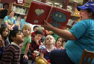Family Fun Party: Children's Librarian Amanda Hairston reads a book to children who participated in the Family Fun Party in honor of Children's Book Week, Thursday evening at the Stewart C.Meyer Library in Harker Heights. - Jaime Villanueva | Herald