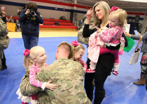 III Corps & 3CR Homecoming: Cpt. Chris Sexton, III Corps, hugs his daughters Maddie, 3, left, and Sadie, 5, right, as his wife Avery Sexton and other daughter Avery, 1, watch during the III Corps and 3rd Cavalry Regiment Homecoming Sunday night at West Fort Hood. - Photo by Herald/MARIANNE GISH