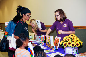 Early Literacy Fair: Nicole Penland (right) works at the Military Child Education Coalition booth during the Early Literacy Fair held at the Stewart C. Meyer Library in Harker Heights on Wednesday morning. - Jodi Perry   Herald