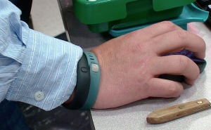 Self-tracking: The wrist of Tim Davis is seen with the FitBit, green, and Nike FuelBand, black, devices he uses to track his physical activity and habits in New Brighton, Pa. - Photo by AP/Noel Waghorn