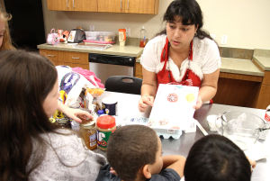 Little And Blooming Chef's Academy: Carly Ross, instructor, shows the receipe for baking cookies during the Little and Blooming Chef's Academy cooking class Monday afternoon at the Harker Heights Activites Center. - Herald/MARIANNE GISH