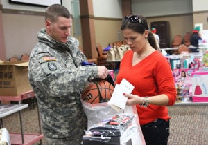 Operation Homefront Toy Distribution: Sgt. Jeryme Stahley, 4th Battalion, 5th Air Defense Artillery Regiment, 69th Air Defense Artillery Brigade, places a basketball into a bag held by his wife Vanessa Stahley during the Operation Homefront's toy distribution for families event Tuesday morning at the Fort Hood Community Event and Bingo Center on Fort Hood. - Herald/MARIANNE GISH