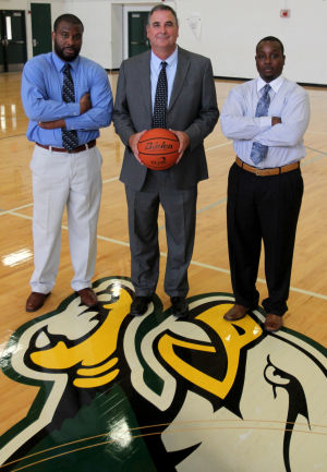 <p>Alberto Jones Jr., left, and Emund Prichett, right, are former players of David Manley, center, who coached at Ellison High School.</p>