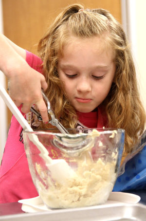 Little And Blooming Chef's Academy: Callie Mathis, 7, scoops cookie dough out to place on a baking sheet during the Little and Blooming Chef's Academy cooking class Monday afternoon at the Harker Heights Activites Center. - Photo by Herald/MARIANNE GISH