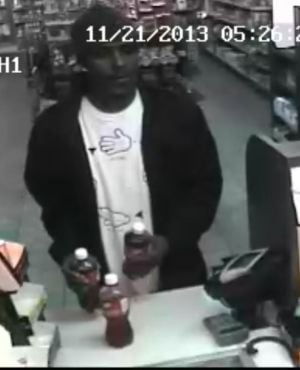 Burglary Suspect: Officers obtained a photo from a store's video surveillance camera showing a black male wearing a dark jacket, dark colored beanie cap, a white tee shirt with hands on the front and jeans. The man used a credit card, which was stolen during a vehicle burglary.