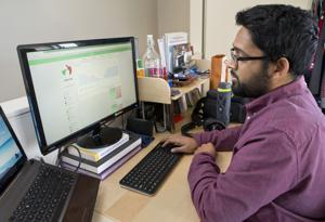 <p>Greg Thomas, 27, checks his stocks performance on the Tip'd Off app at home in Sunnyvale, Calif., on Dec. 24.</p>