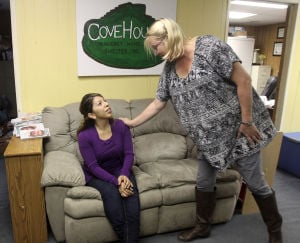 Cove House: Belinda Parilla, left, Cove House manager, wipes her eyes while speaking with Mary Claire Huslage, a Cove House volunteer, at the shelter Thursday. - Herald/CATRINA RAWSON