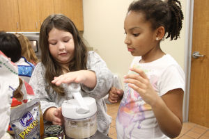 Little And Blooming Chef's Academy: Brooke Ross, 8, left, pushes down on a mixer as Emma Atterberry, 9, watches during the Little and Blooming Chef's Academy cooking class Monday afternoon at the Harker Heights Activites Center. - Herald/MARIANNE GISH