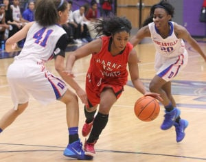 <p>Harker Heights' Angela DeLaney dribbles through Duncanville defenders during a playoff game.</p>