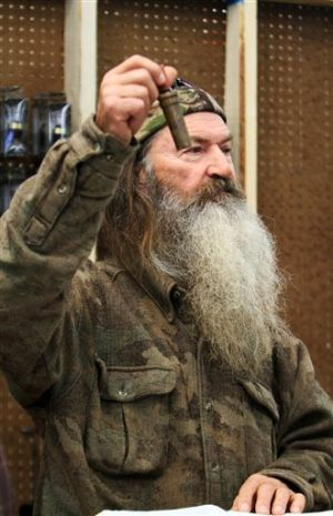 "Duck Commander 1 Millionth Duck Call: File-This Nov. 7, 2013 file photo shows Phil Robertson, the Duck Commander, holding the 1 millionth duck call assembled for 2013 at company's warehouse in West Monroe, La. The A&E channel says ""Duck Dynasty"" patriarch Robertson is off the show indefinitely after condemning gays as sinners in a magazine interview. In a statement Wednesday, Dec. 18, 2013, A&E said it was extremely disappointed to read Robertson's comments in GQ magazine. (AP Photo, The News-Star/Margaret Croft) NO SALES - MARGARET CROFT/THE NEWS-STAR"